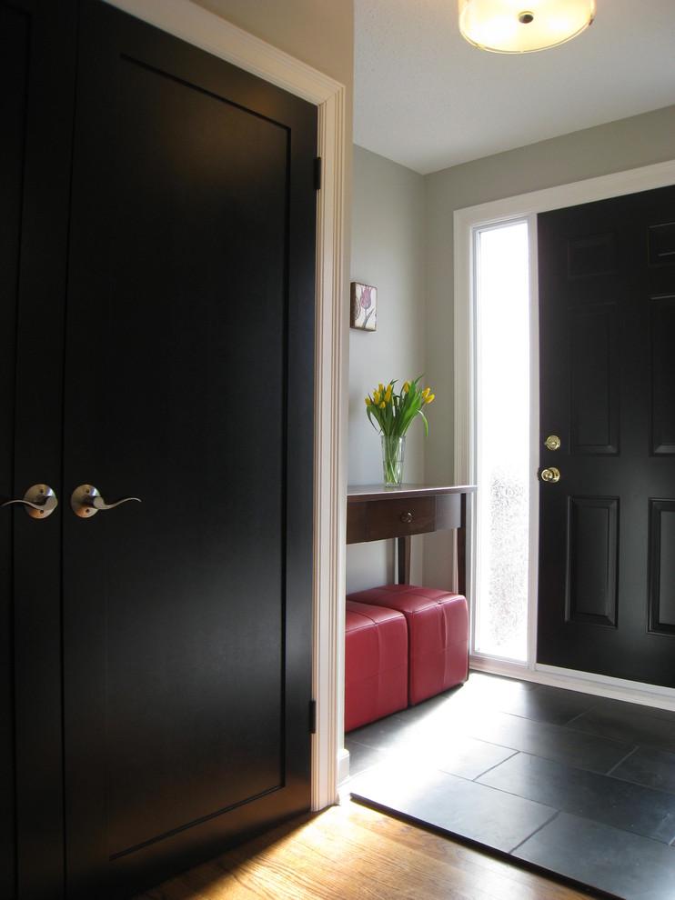 Entryway - traditional black floor entryway idea in Montreal with a black front door