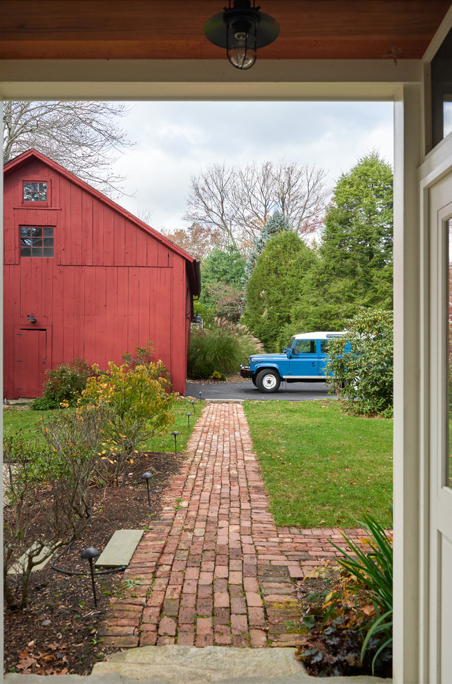Example of a large farmhouse dark wood floor and brown floor entryway design in New York with white walls and a green front door
