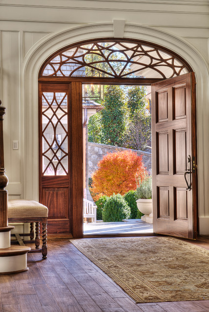 Entryway - large traditional medium tone wood floor entryway idea in Other with white walls and a medium wood front door
