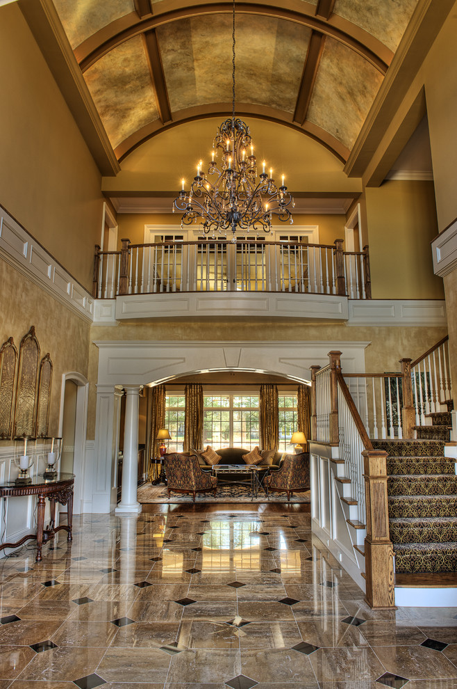 Example of a huge classic limestone floor foyer design in Other with yellow walls