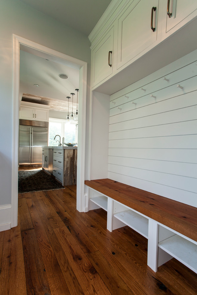 Inspiration for a mid-sized country medium tone wood floor mudroom remodel in Philadelphia with white walls