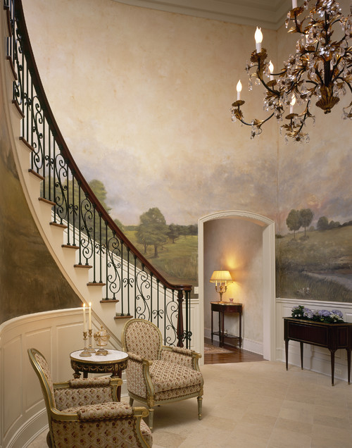 Curved traditional staircase with huge landscape mural on the wall and iron railing