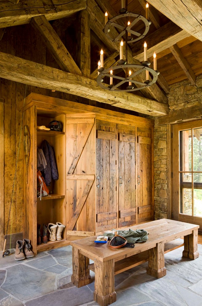 Example of a mountain style mudroom design in Other with a glass front door