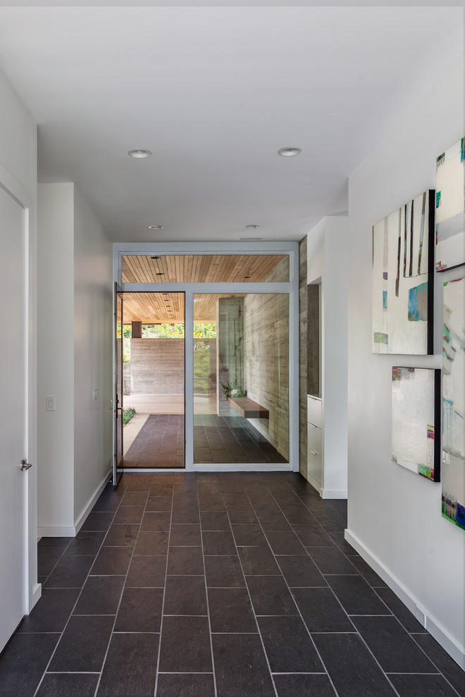 Example of a mid-sized trendy porcelain tile entryway design in Charleston with white walls and a dark wood front door