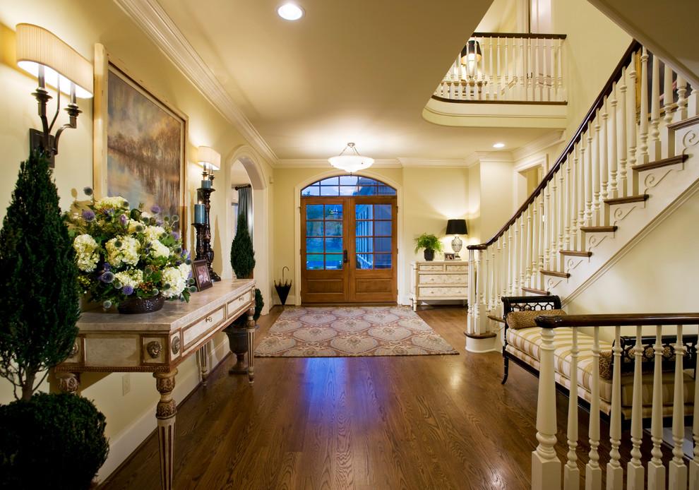 Elegant medium tone wood floor entryway photo in Philadelphia with beige walls and a glass front door