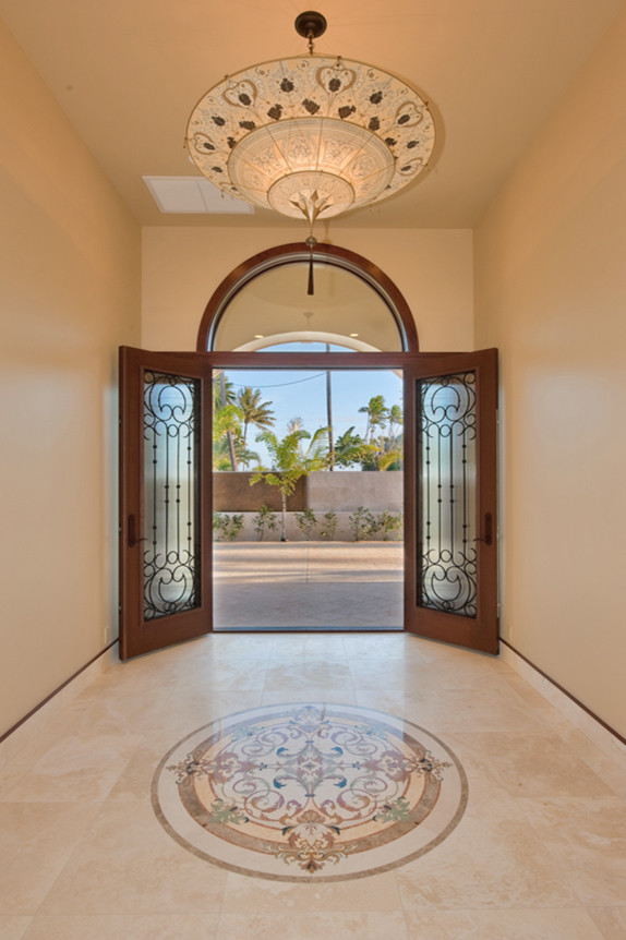 Inspiration for a mid-sized modern travertine floor entryway remodel in Hawaii with beige walls and a dark wood front door