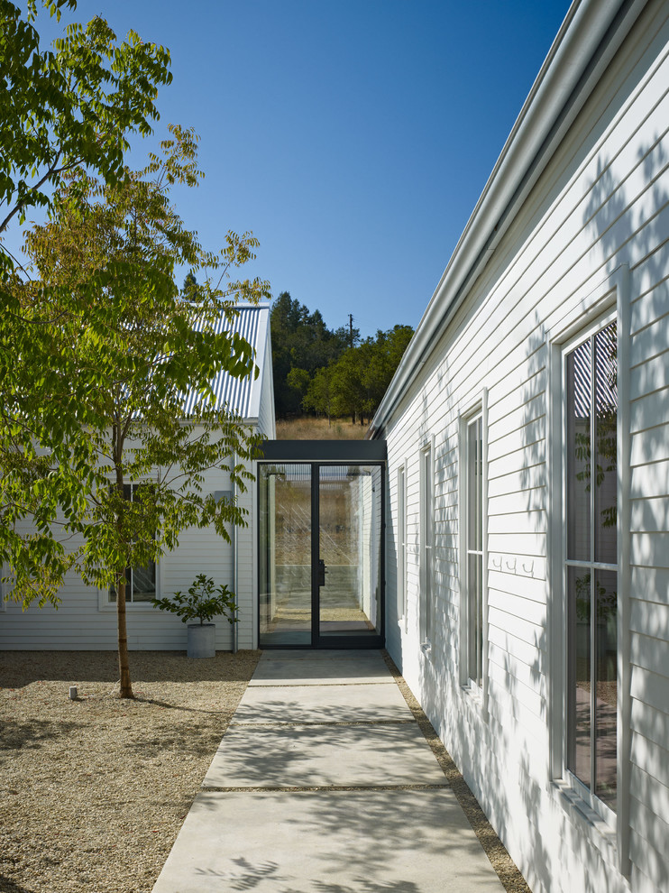 Example of a cottage entryway design in San Francisco with a glass front door
