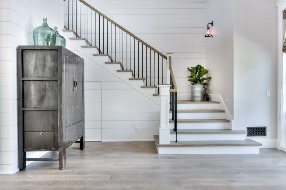 Inspiration for a large country medium tone wood floor and gray floor foyer remodel in Orange County with white walls