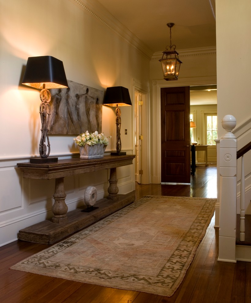 Example of a mid-sized classic medium tone wood floor foyer design in Charleston with yellow walls