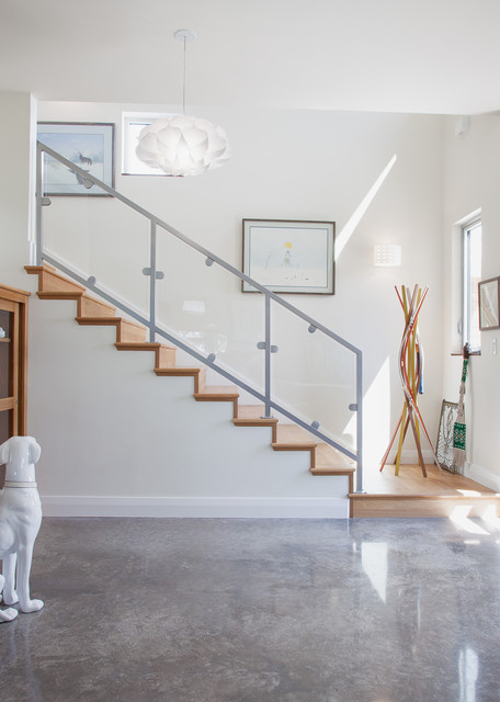 Example Of A Trendy Concrete Floor And Gray Entryway Design In Austin