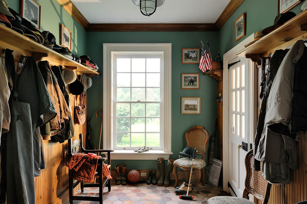 Example of a french country terra-cotta tile mudroom design in New York