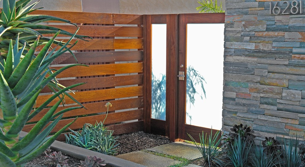 Example of a trendy entryway design in Orange County with a glass front door