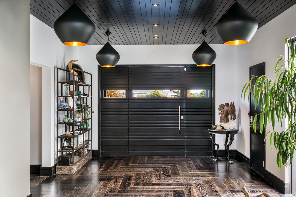Example of a mid-sized trendy dark wood floor entryway design in San Francisco with white walls and a black front door