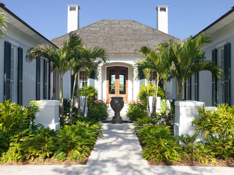 Imagen de puerta principal tropical, de tamaño medio, con paredes blancas, puerta doble y puerta de madera en tonos medios