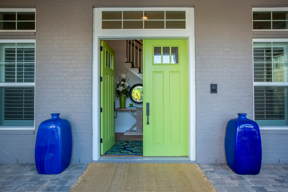 Example of a large beach style entryway design in Jacksonville with gray walls and a green front door
