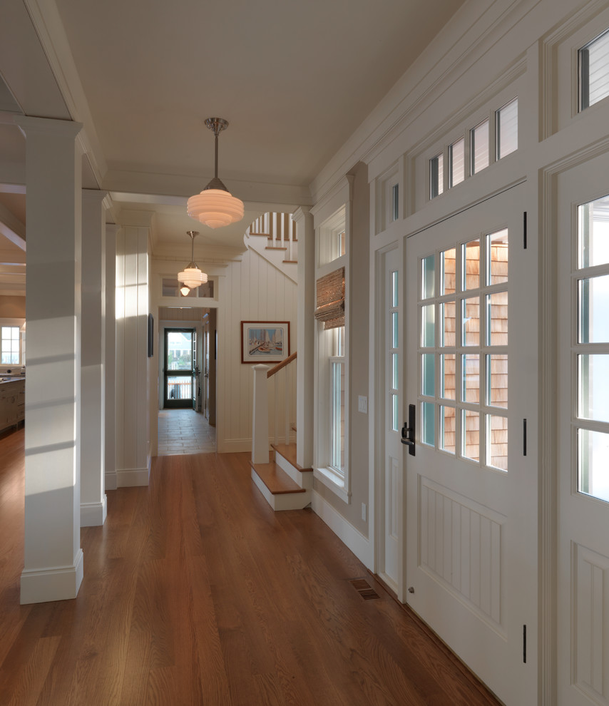 Inspiration for a timeless medium tone wood floor entryway remodel in Newark with white walls and a white front door