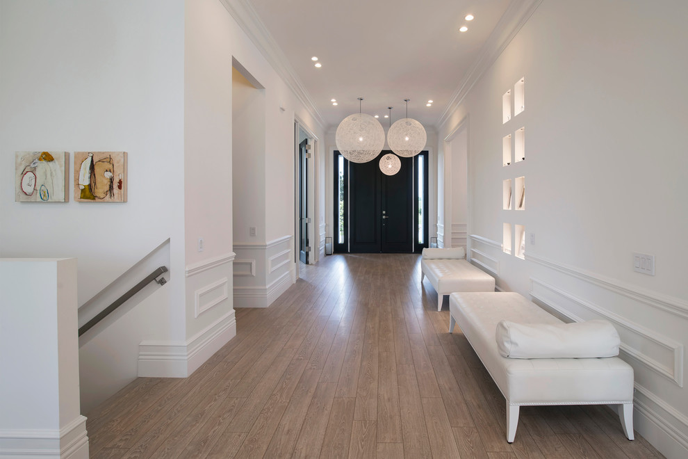 Example of a large trendy light wood floor entryway design in DC Metro with white walls and a black front door