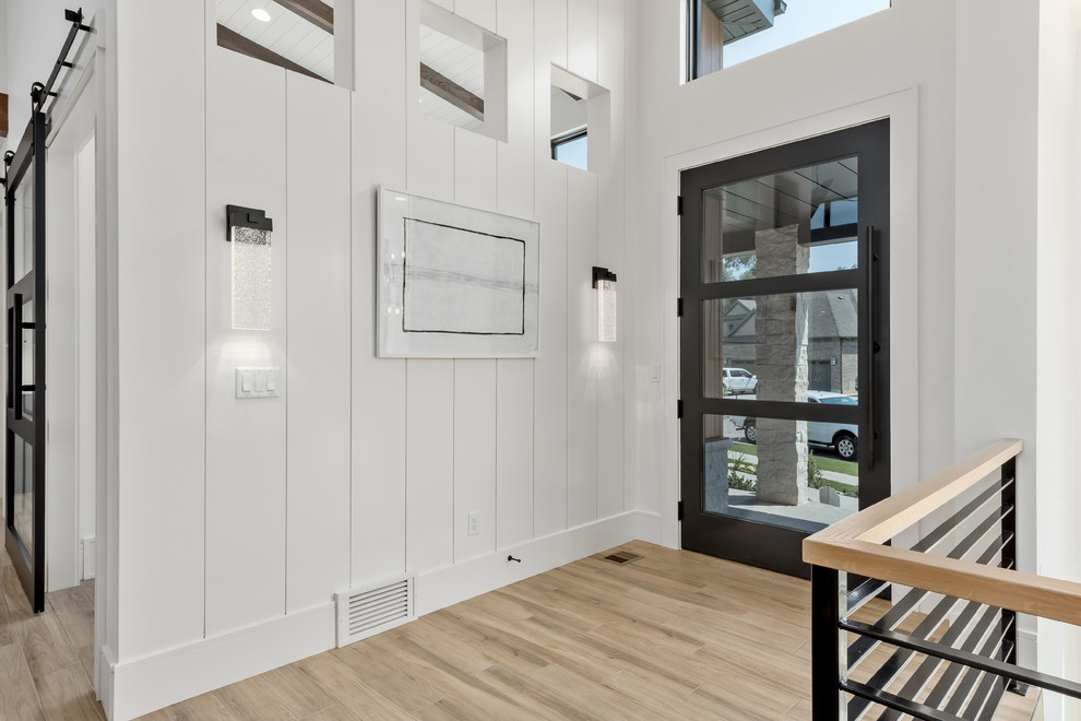 Example of a large trendy porcelain tile and beige floor entryway design in Salt Lake City with white walls and a black front door