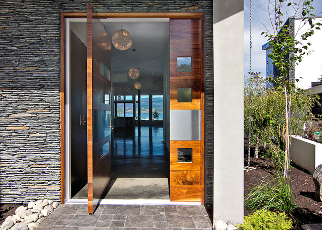 Trendy Pivot Front Door Photo In Vancouver With A Medium Wood