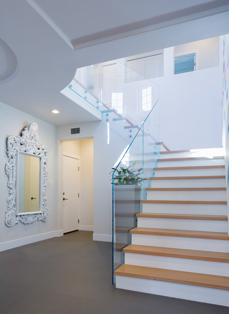 Inspiration for a mid-sized contemporary porcelain floor entryway remodel in Orange County with white walls and a dark wood front door