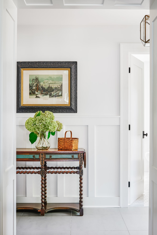 Example of a mid-sized beach style porcelain tile and gray floor entryway design in Toronto with white walls and a white front door