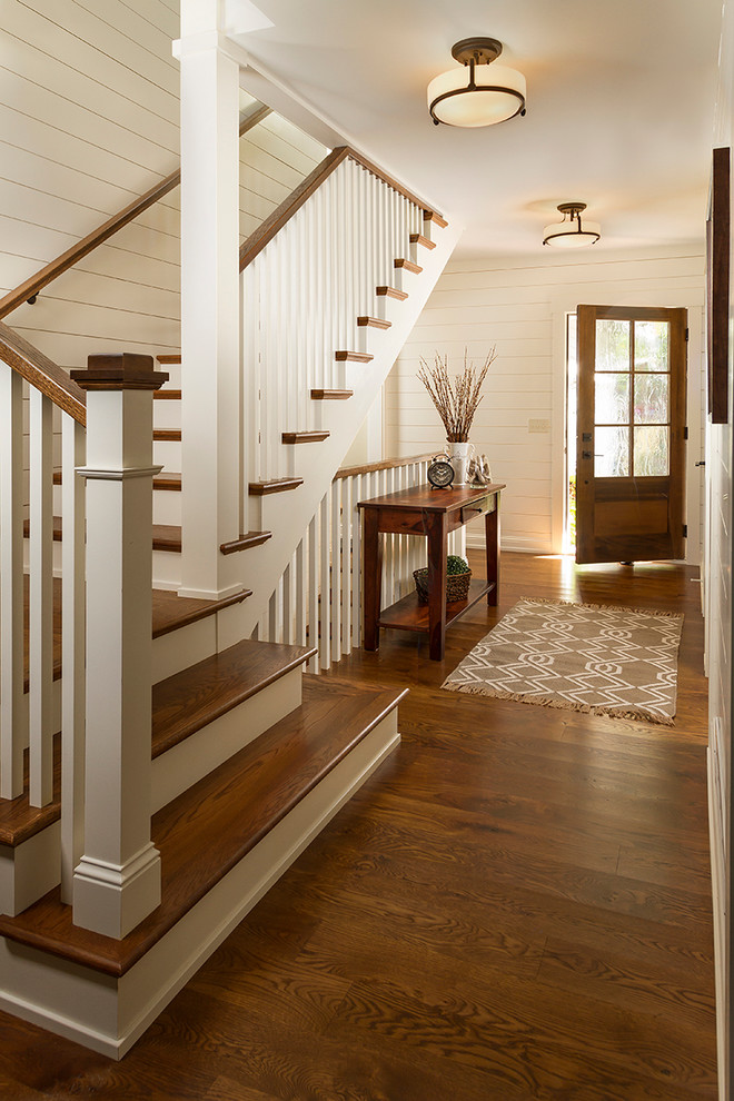 Example of a mid-sized classic medium tone wood floor entryway design in Minneapolis with white walls and a dark wood front door