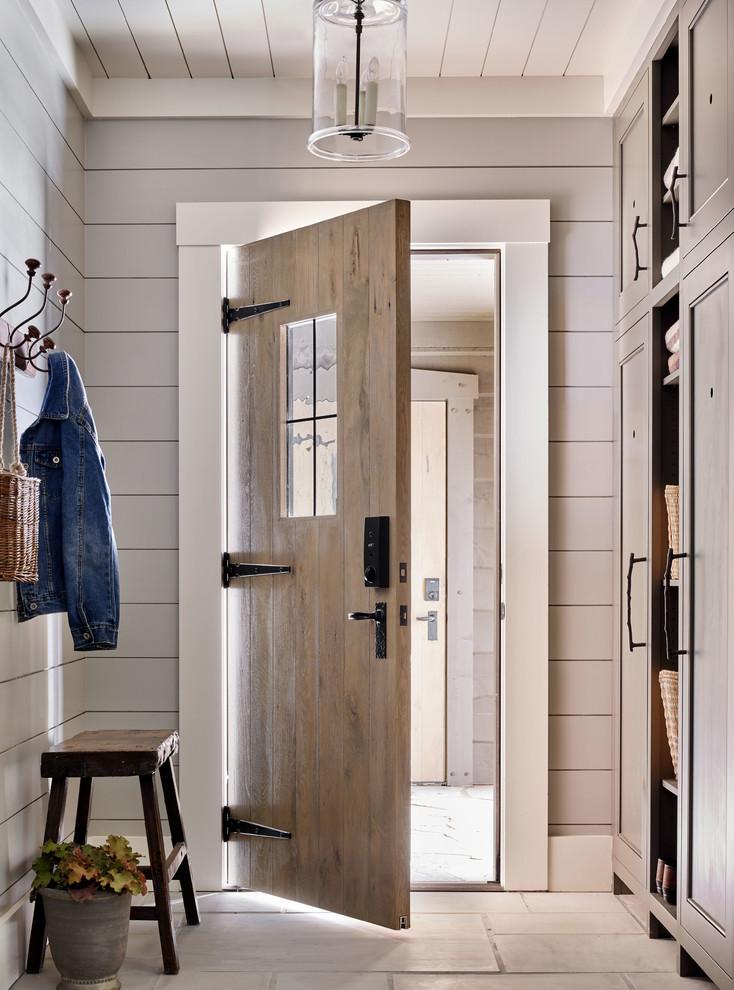 Entryway - rustic gray floor entryway idea with gray walls and a medium wood front door