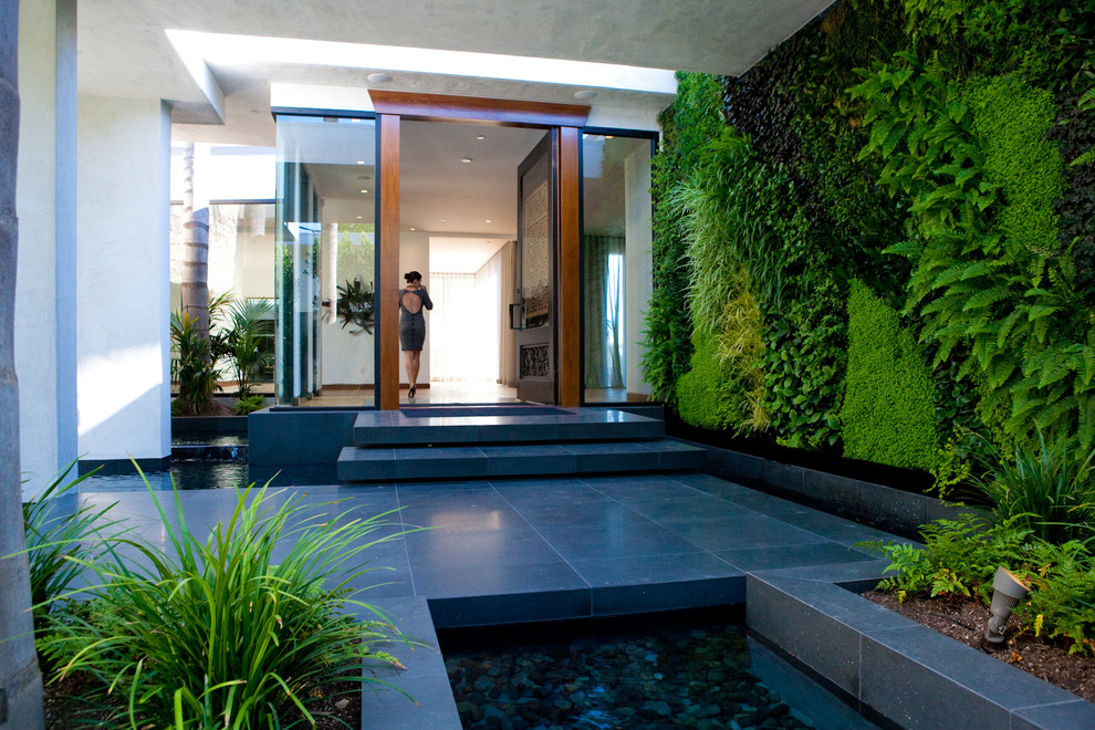 Entryway - large contemporary beige floor entryway idea in Los Angeles with a glass front door and gray walls