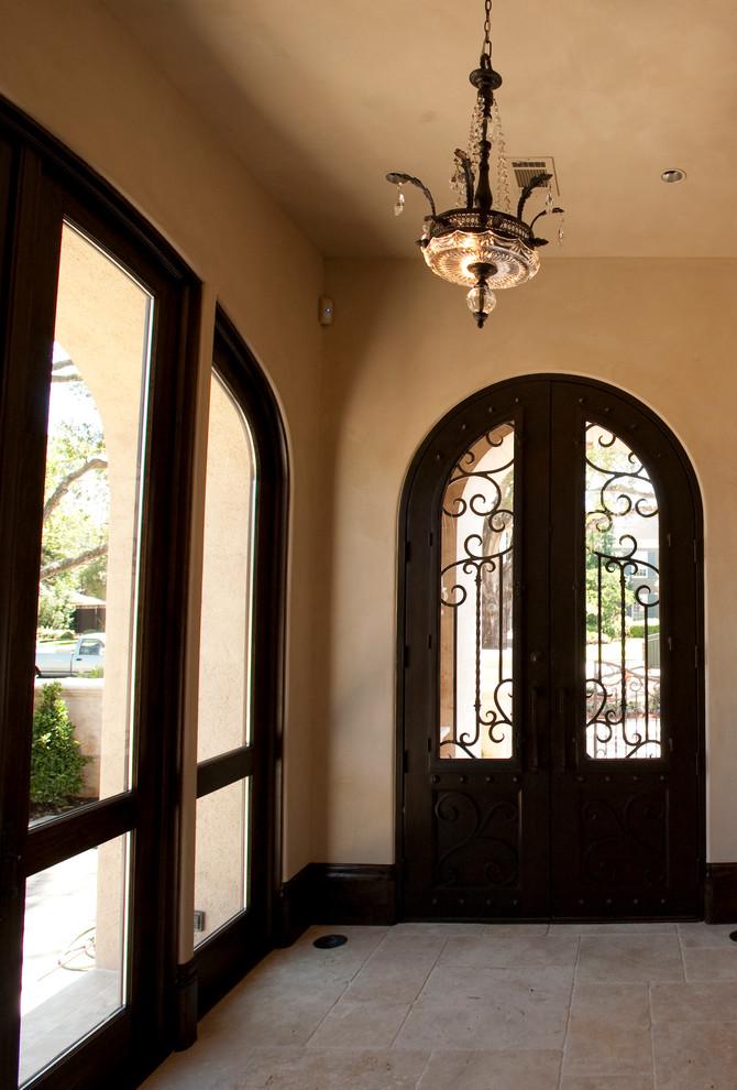 Ejemplo de puerta principal mediterránea, extra grande, con paredes beige, suelo de travertino, puerta doble y puerta de madera oscura