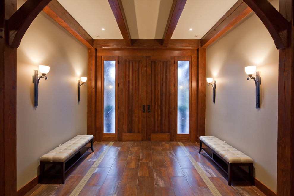 Elegant entryway photo in Vancouver with white walls and a dark wood front door