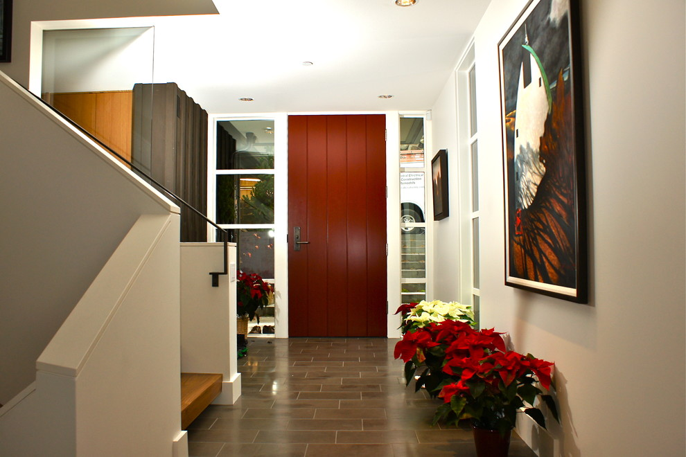 Example of a trendy ceramic tile and gray floor entryway design in Seattle with a red front door