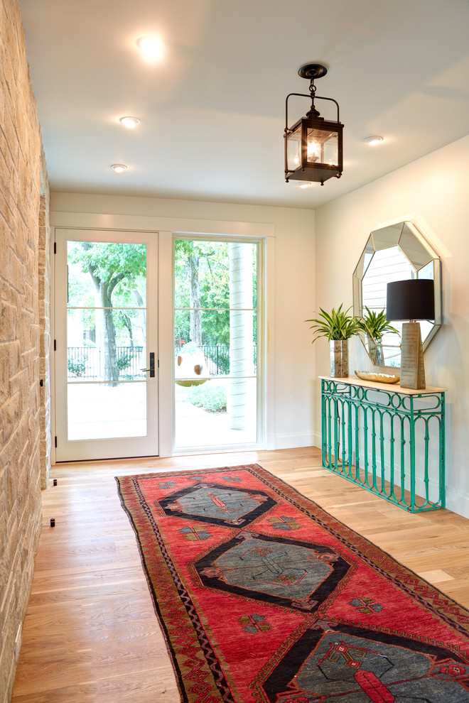 Entryway - large transitional light wood floor entryway idea in Austin with white walls and a white front door