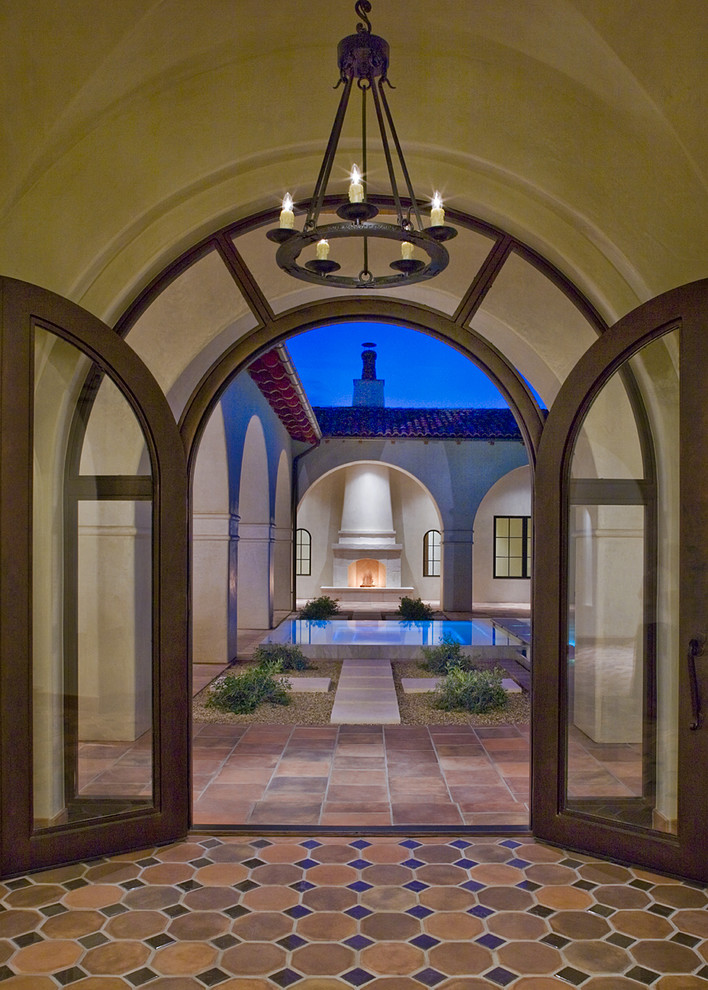 Inspiration for a mediterranean double front door remodel in Austin with a glass front door
