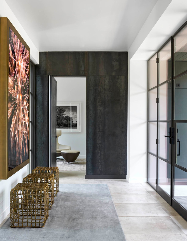 Example of a large trendy gray floor and concrete floor entryway design in Dallas with white walls and a glass front door