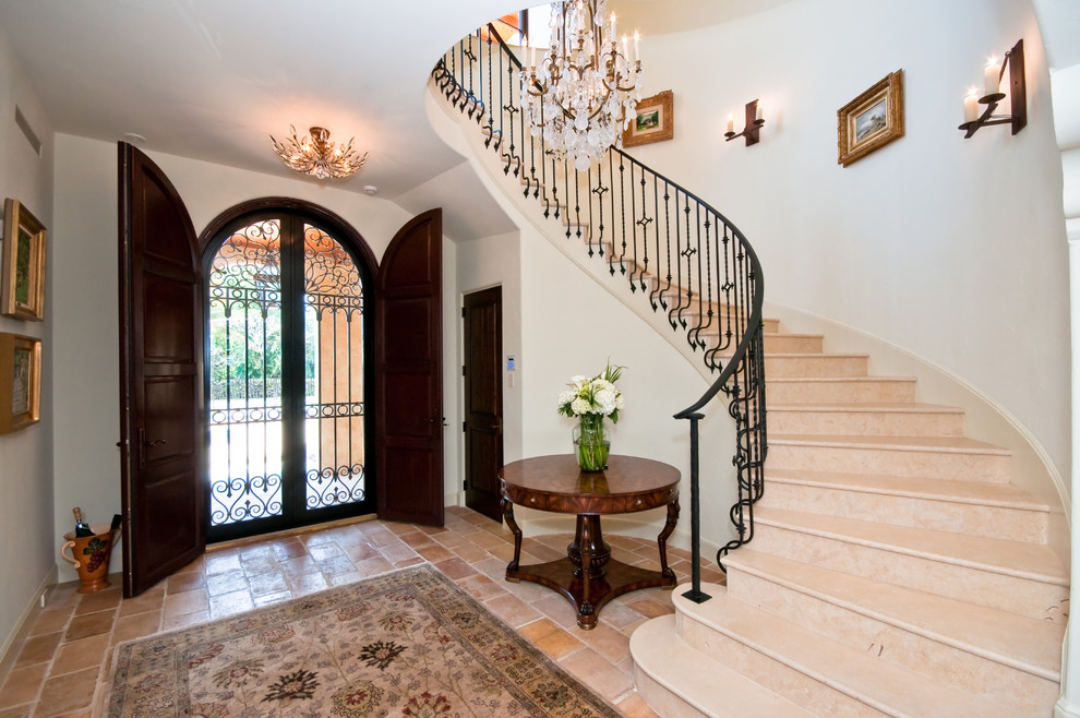 Inspiration for a large mediterranean ceramic tile entryway remodel in Miami with a dark wood front door and white walls