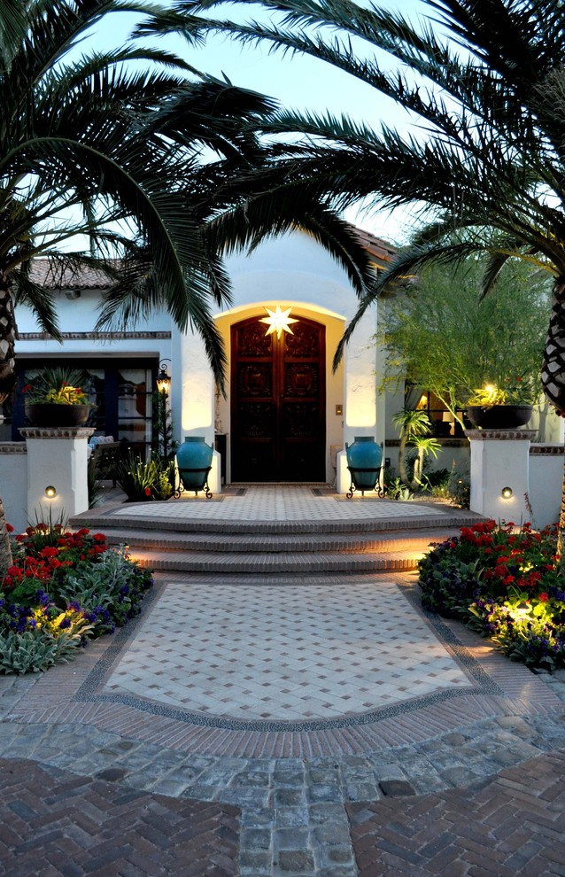 Inspiration for a mediterranean double front door remodel in Phoenix with a dark wood front door