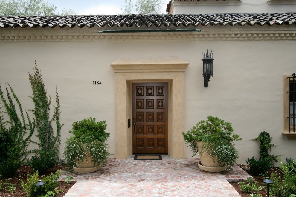 Inspiration for a mediterranean entryway remodel in Other with a dark wood front door