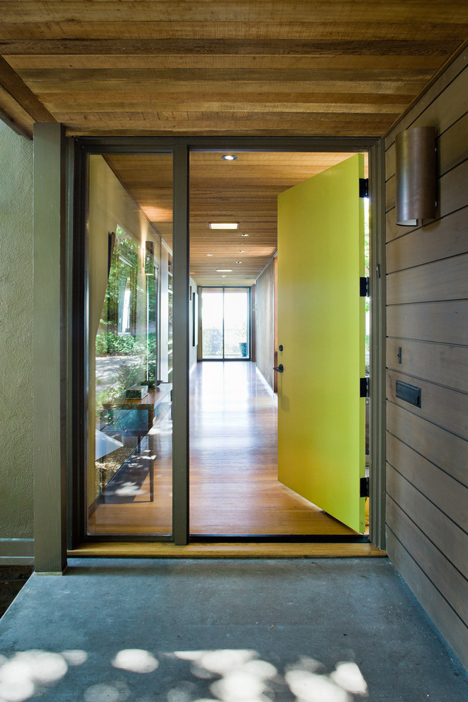 Large minimalist concrete floor entryway photo in San Francisco with a green front door and brown walls