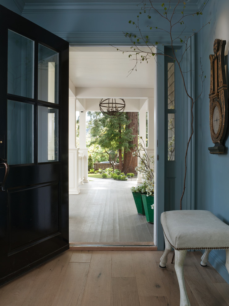 Example of a classic beige floor entryway design in San Francisco with a black front door and blue walls