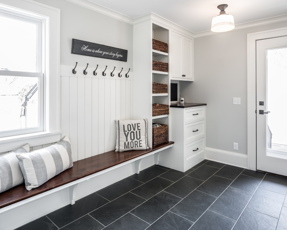 Inspiration for a farmhouse black floor entryway remodel in Minneapolis with gray walls and a glass front door