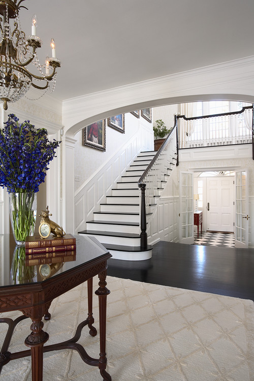 large white traditional foyer with dark wood floors wood entry table on beige rug and oversized artwork on the staircase wall