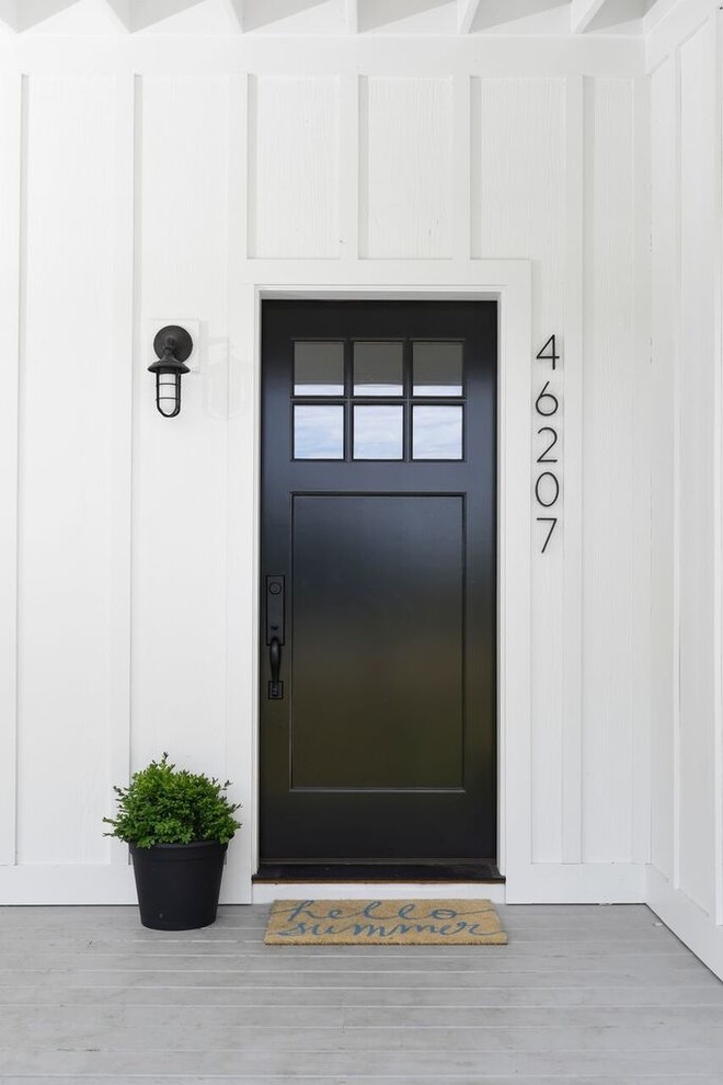 Example of a farmhouse entryway design in Chicago with a black front door