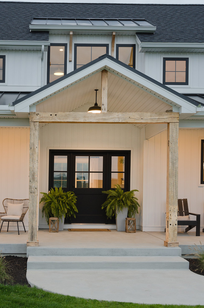 Entryway - mid-sized cottage concrete floor and gray floor entryway idea in Other with a black front door and white walls
