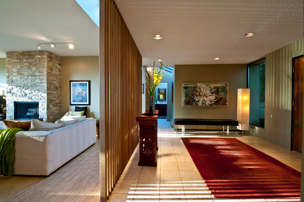 Entryway - large modern travertine floor and beige floor entryway idea in Vancouver with green walls and a medium wood front door