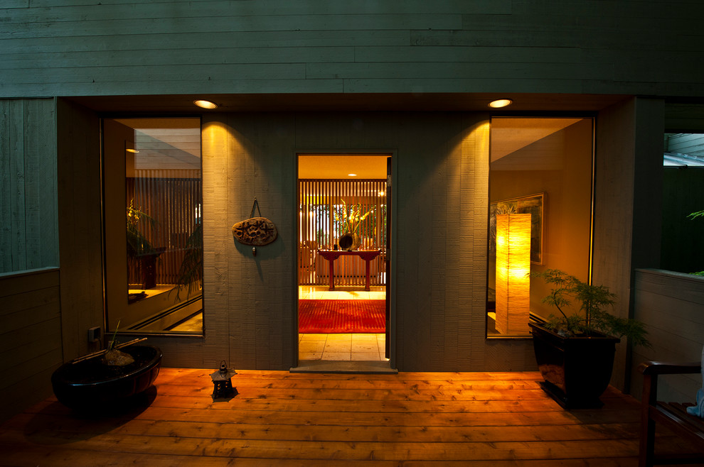 Example of a large minimalist travertine floor entryway design in Vancouver with green walls and a medium wood front door