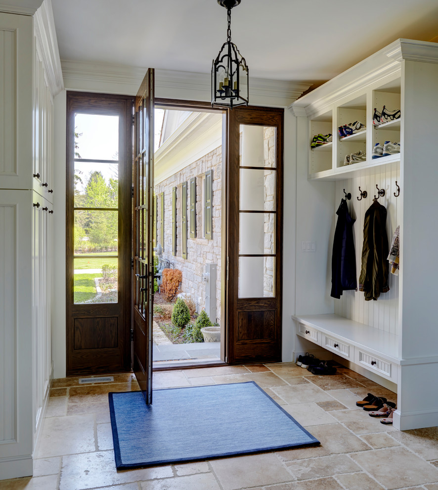 Large elegant limestone floor and beige floor entryway photo in Milwaukee with white walls and a dark wood front door
