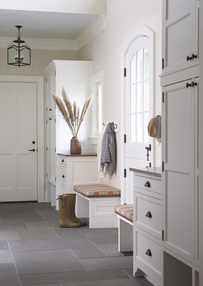 Example of a large cottage slate floor and gray floor entryway design in New York with white walls and a white front door
