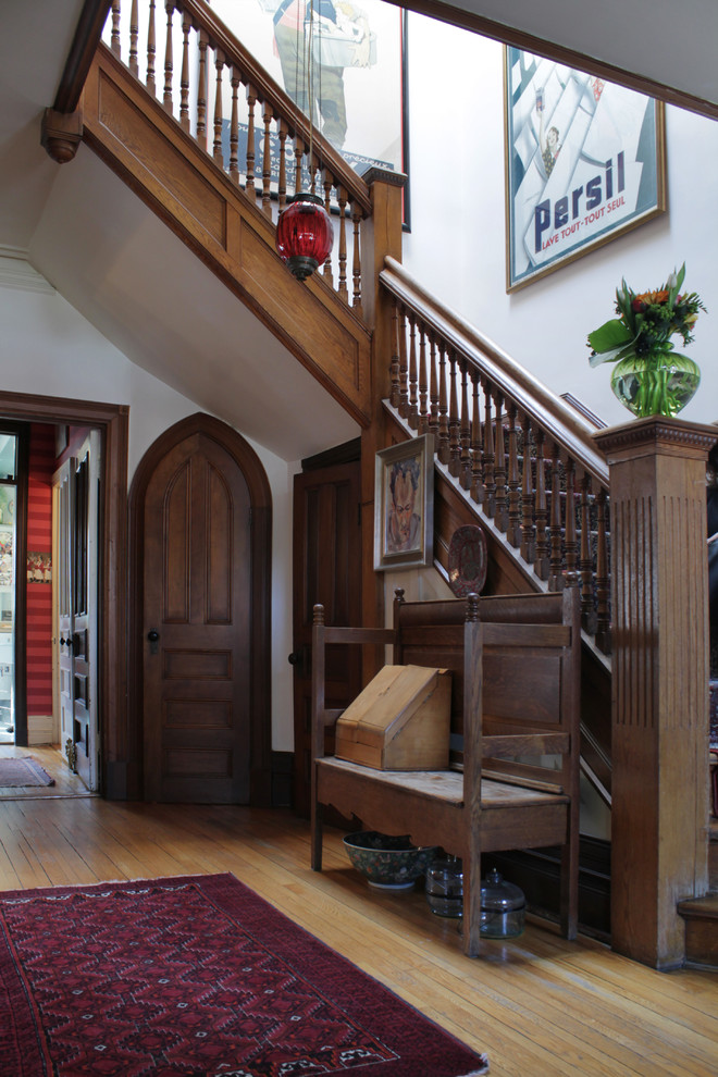Inspiration for a victorian light wood floor foyer remodel in Montreal with white walls