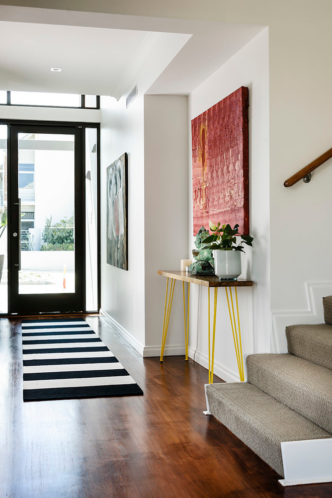 Example of a trendy dark wood floor entryway design in Perth with white walls and a glass front door