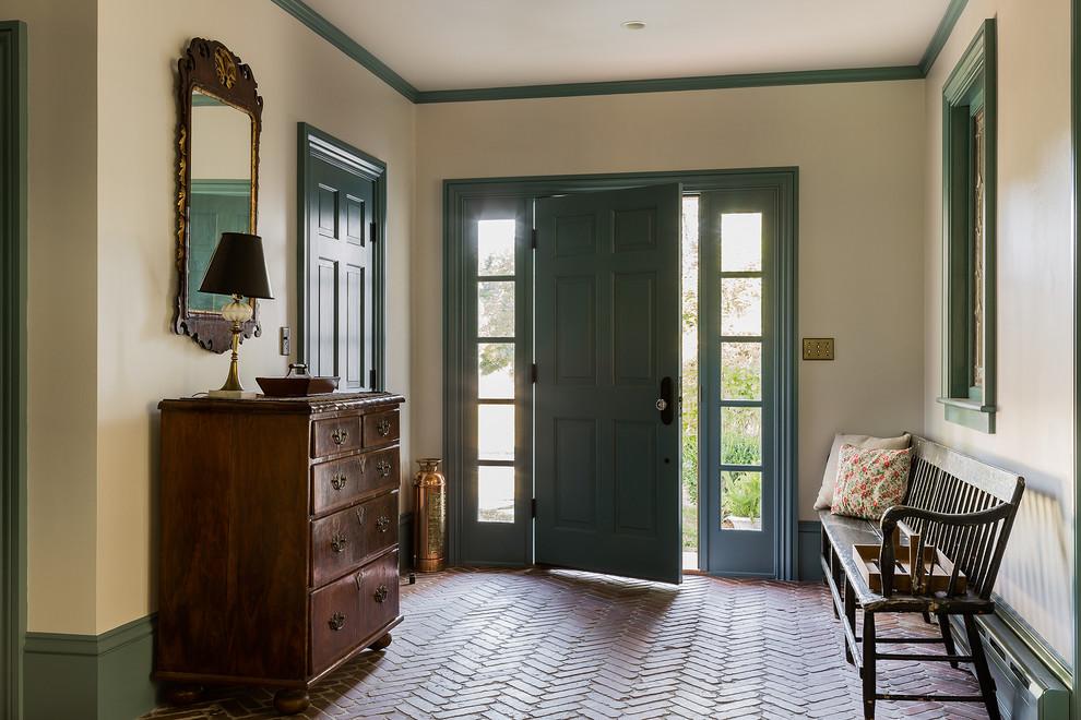 Elegant brick floor entryway photo in Boston with a blue front door and beige walls